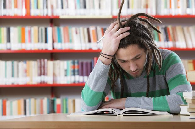 Guy with his hand in is head trying to concentrate on a book