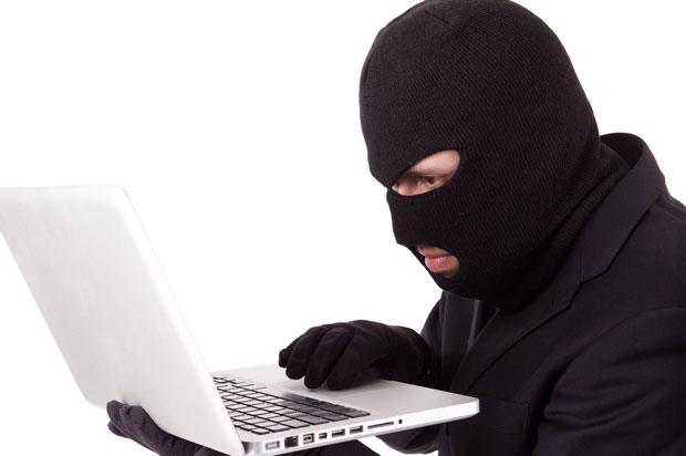 Man on a laptop wearing a balaclava.