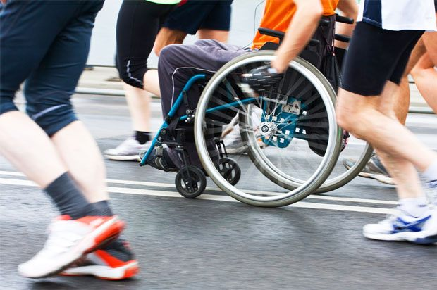 One person in a wheelchair surrounded by people running
