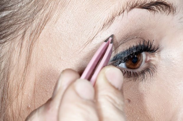 Close up of girl plucking her eyebrows with tweezers