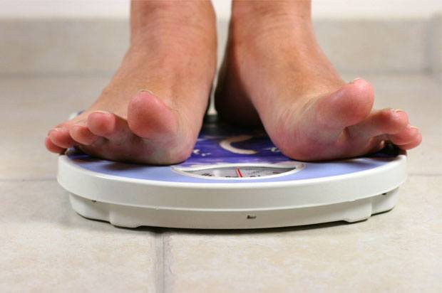 Feet of someone standing on blue weighing scales