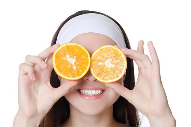 Girl with fruit held over her eyes