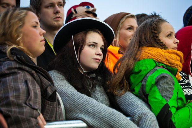 Girl wearing hat looking sad in festival crowd