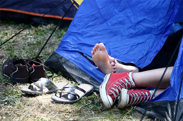 Two pairs of feet poking out of a tent