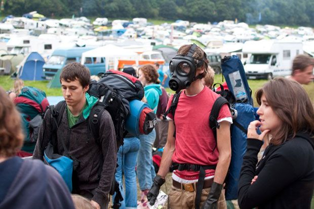 Group of people with backpacks one wearing a gas mask