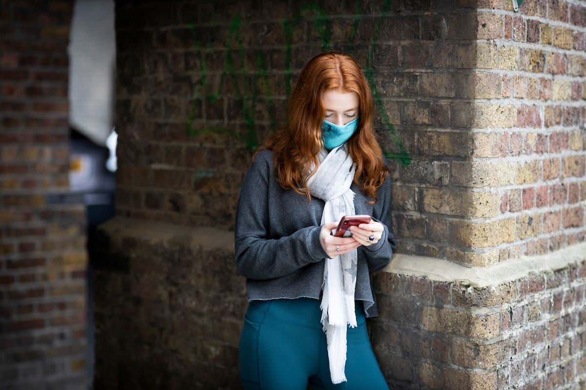 A red-headed young woman is leaning on a brick wall. She is looking up how to get help for addiction. She is wearing a white scarf, a grey zip-up and a blue mask. The photo is cut-off at her waist.