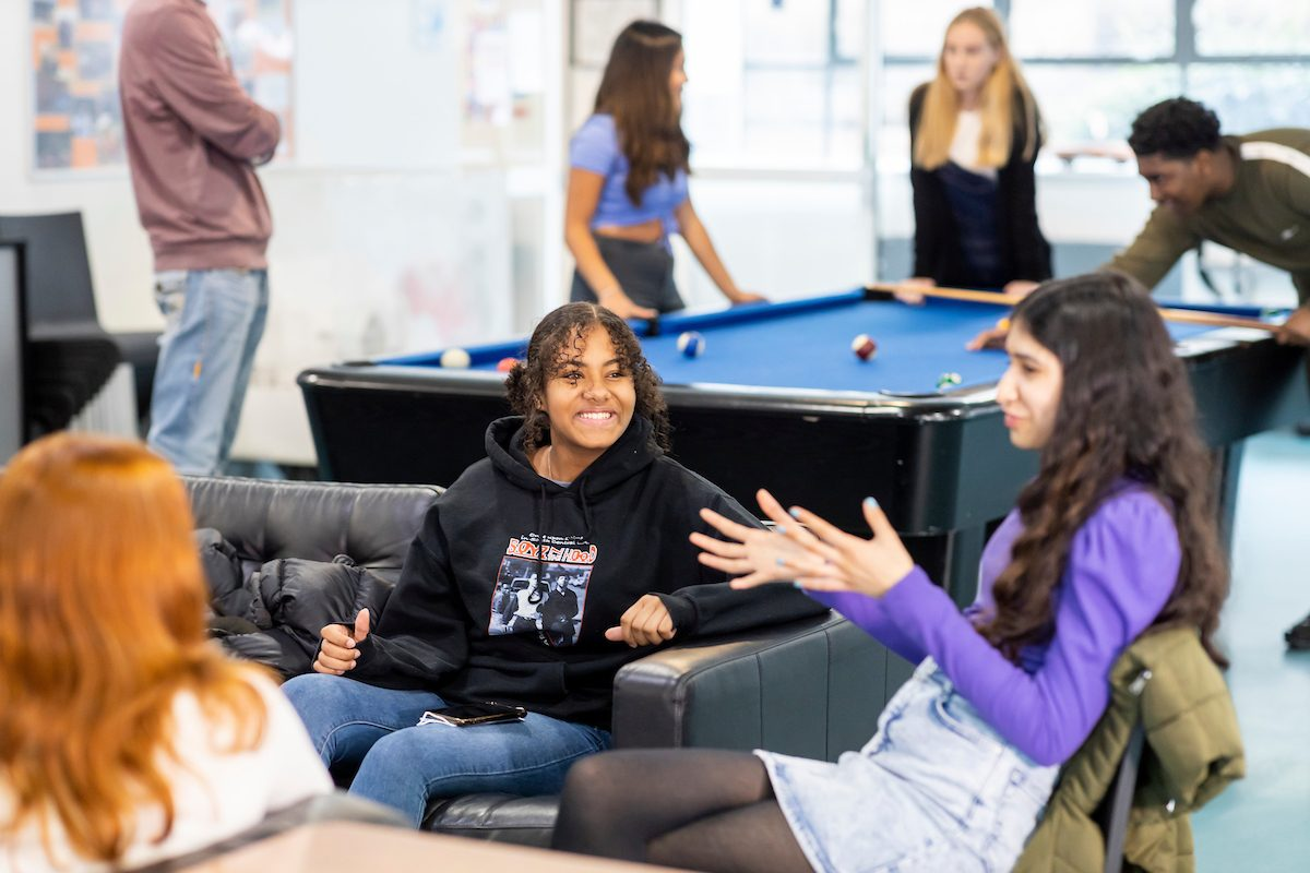 a group of young women are sitting on a sofa. The one in the middle is explaining how to get high at home. They are laughing. This is a wide-angle image.
