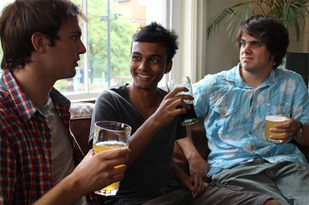 Three boys on a sofa chatting and having a drink
