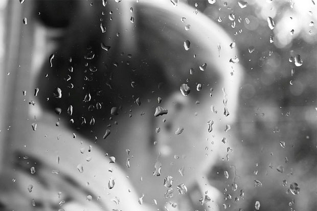 Black and white, girl sat behind rain splattered window