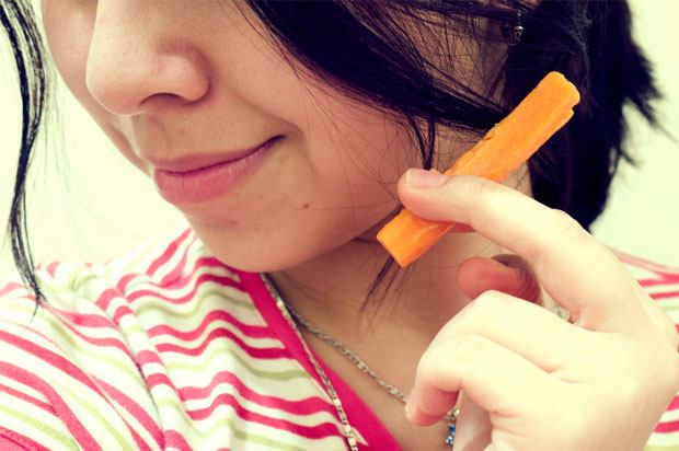 Girl holding a carrot between her fingers like she's smoking