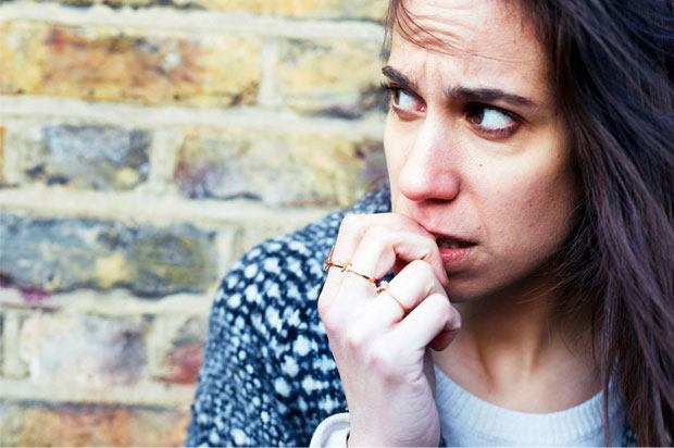 brick background with girl biting her nails