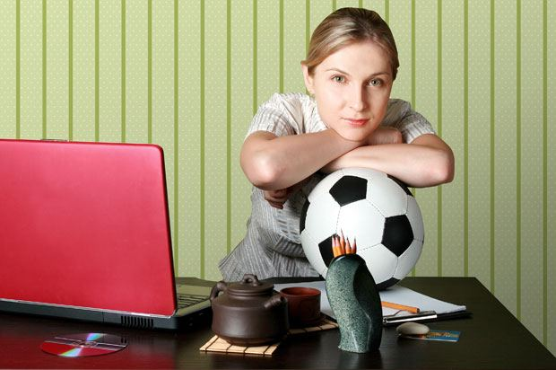 Woman with a football in the office.