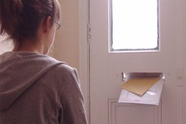 girl watching post come through letter box
