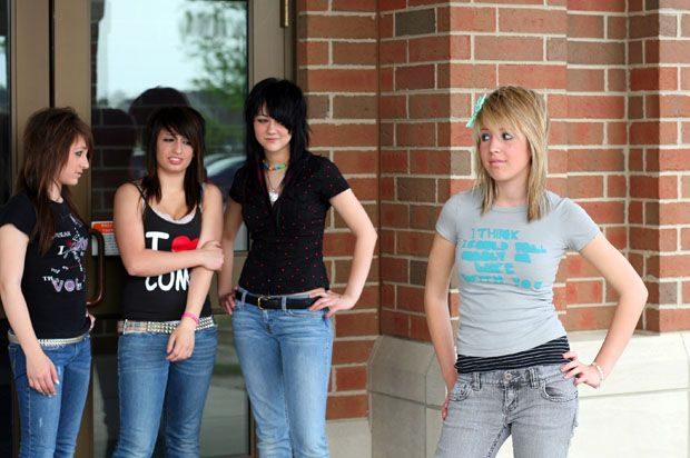 three girls wearing black with black hair staring at a blonde girl with a grey t-shirt.