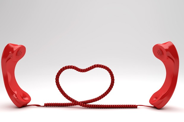 Two phones with the cord in the shape of a heart.