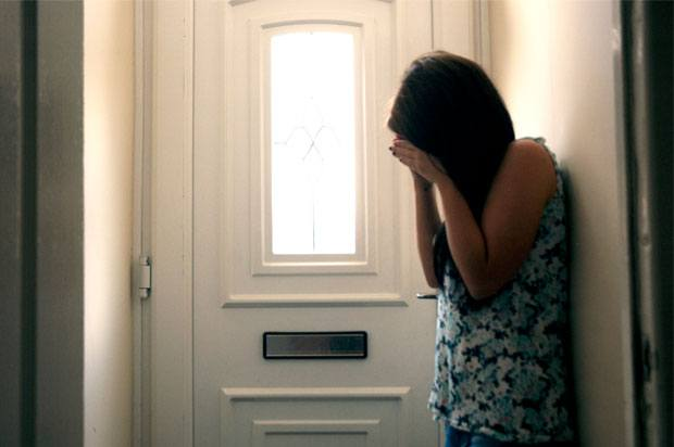 Girl with head in her hands, standing by the front door of a house.