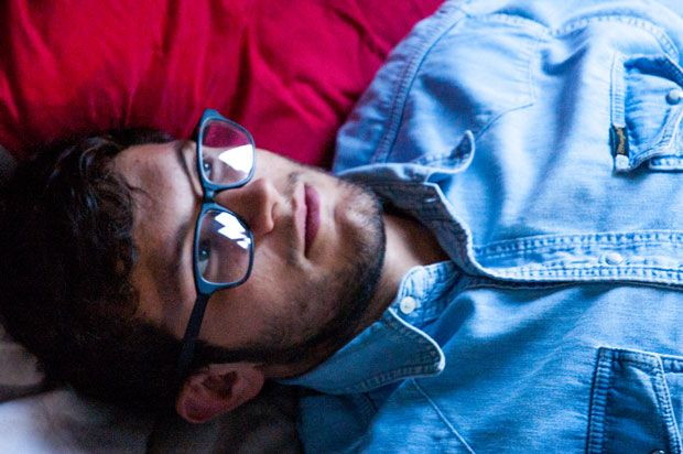 Guy with glasses and a denim shirt lying on his bed