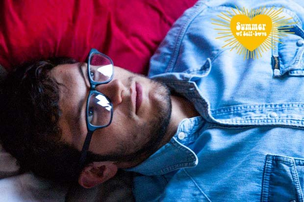 Guy with glasses and a denim shirt lying down on his bed
