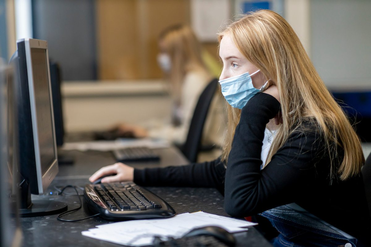 A young, blonde woman is sitting at a desktop. She is wearing a mask. She is researching Crystal Meth. This is a wide-angle image.