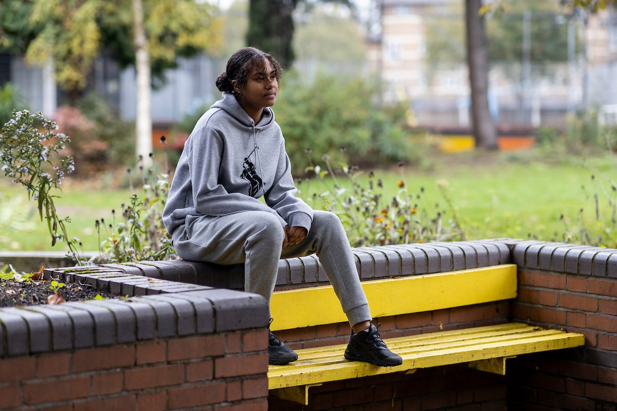 A young woman is sitting on a brick wall, on top of a bench. She is thinking about getting money from drugs. This is a full-body image.