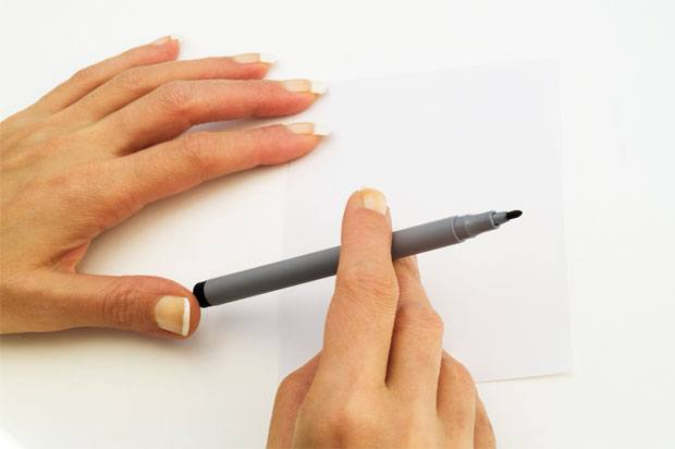 hands holding a pen with carefully manicured nails.