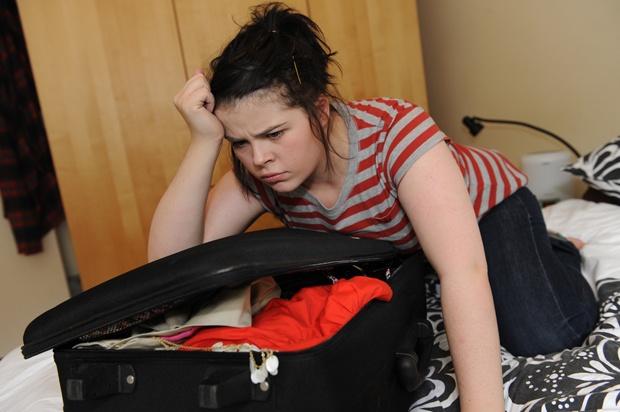 Girl in bedroom packing