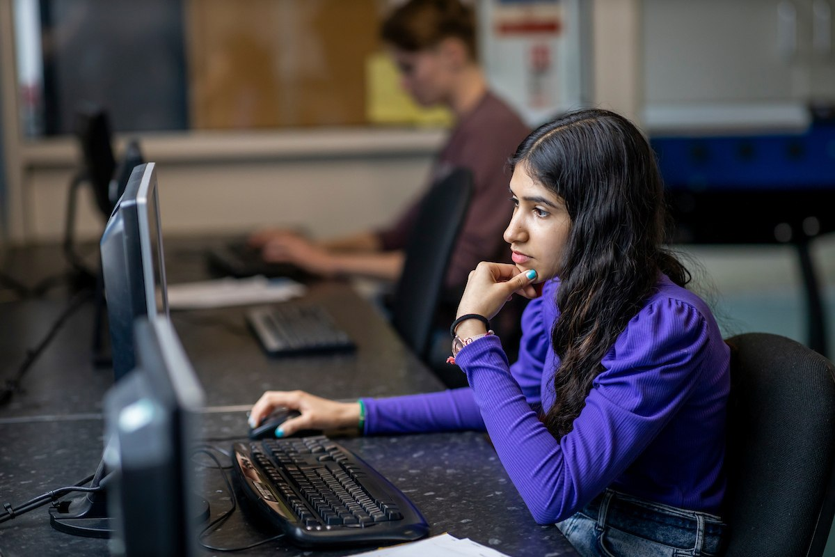 A young woman is sitting at a desktop. She is looking up nos balloons. This is a wide-angle image.