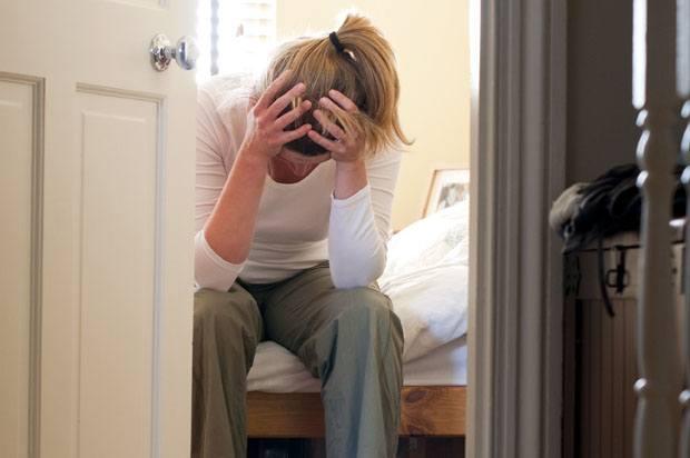 Woman sat behind door on her bed with her head in her hands.