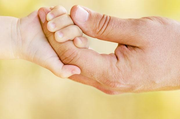 Man's hand holding baby's hand.