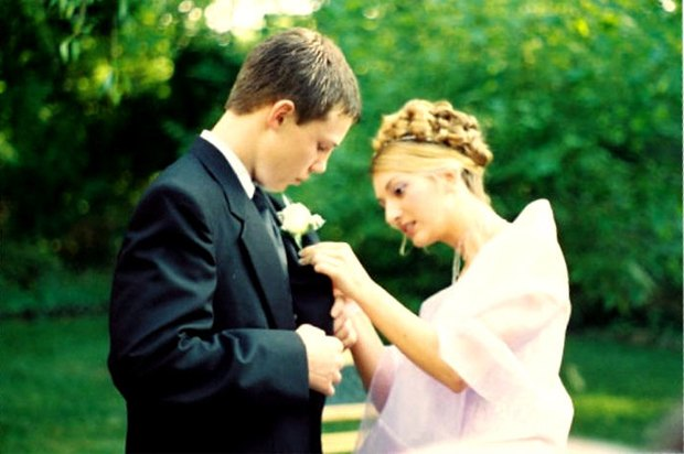 girl in prom dress pinning a corsage onto a boy's tux