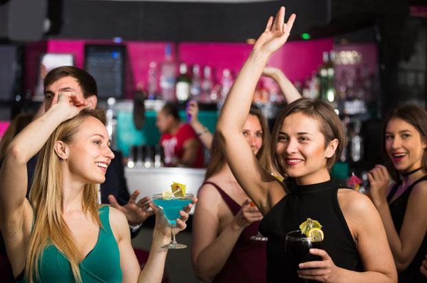 group of women dancing in a club with drinks in their hands.
