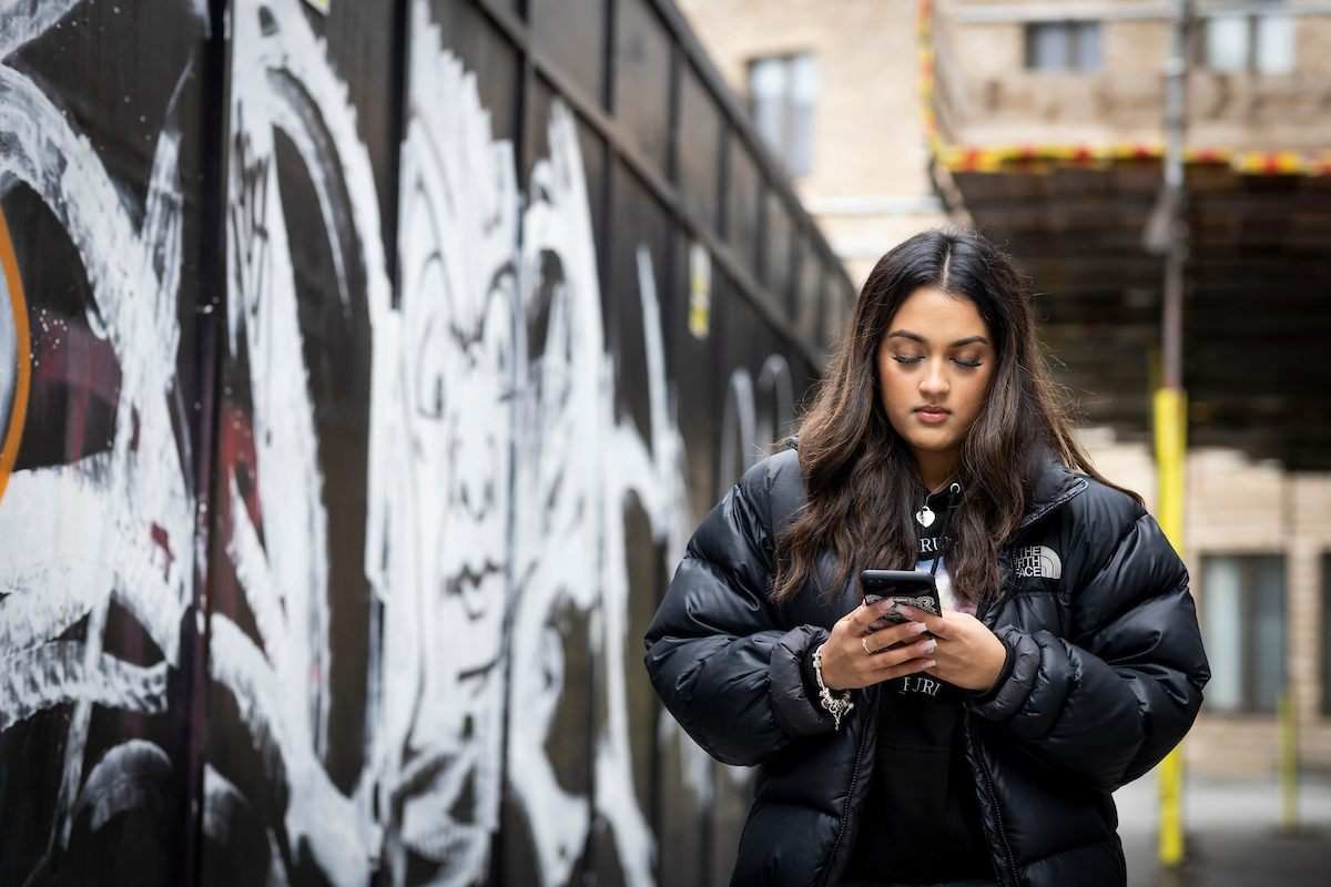 A young woman is walking down the street. She is staring at her phone, trying to find rehab options. She is wearing a black puffer jacket. This is a close-up image.