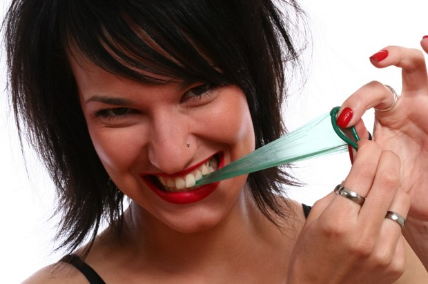 Girl pulling at a condom with her teeth.