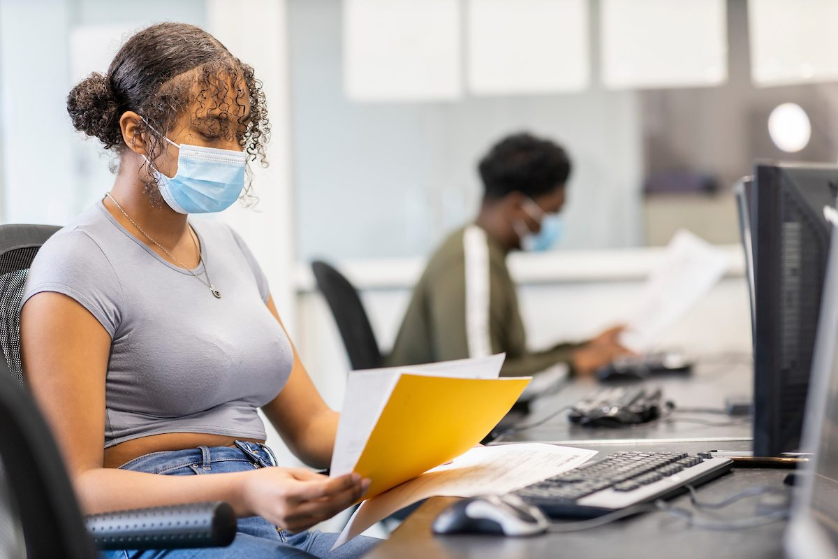 A young woman is sitting at a desk, reading a piece of paper. It is about Salvia and legal highs. She is wearing a mask. This is a wide-angle image.