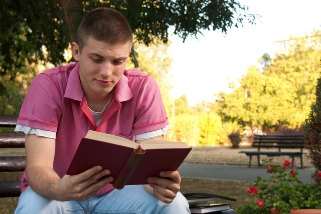 a young man sat on a bench reading a book outside