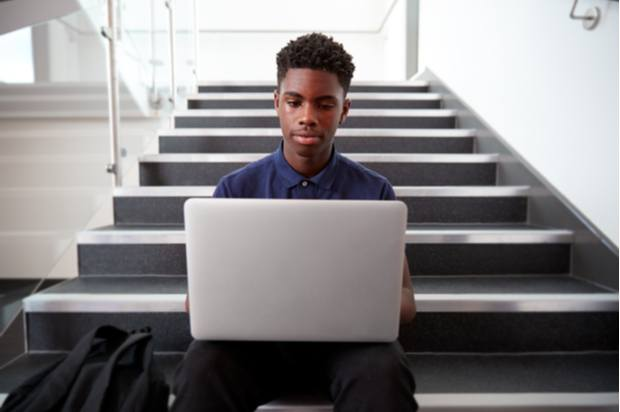 A young person sits on the stairs using their laptop