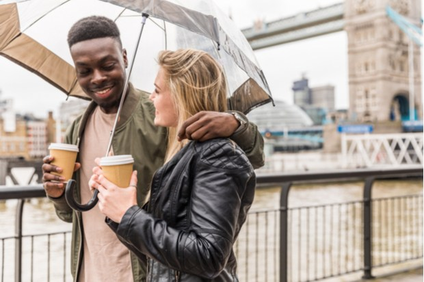 A young couple walk arm in arm, holding an umbrella and coffee cups