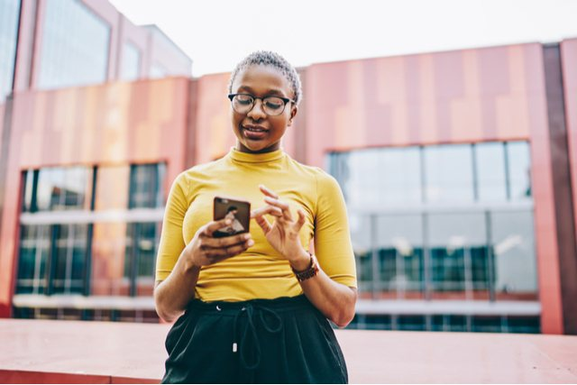 a young woman with glasses on in a yellow top checking her phone.