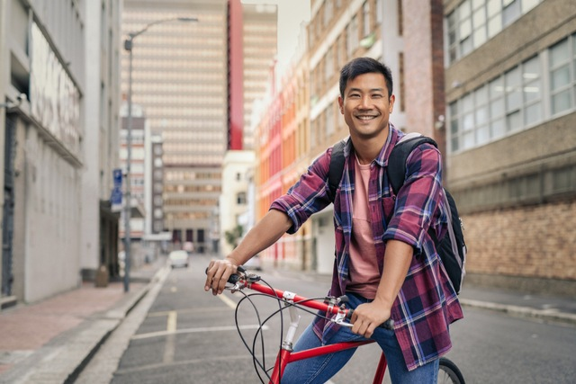 A young man with a bike smiling at the camera in an alleyway
