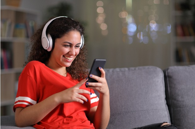 A young person sits on their sofa wearing a red t-shirt and headphones; they are looking at their phone and smiling