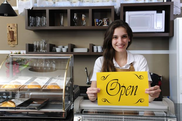 Girl in shop holding the open sign.