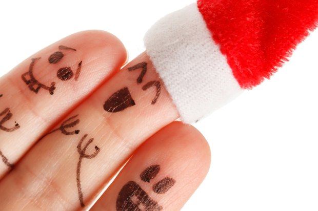 three fingers with faces drawn on and a Christmas hat.