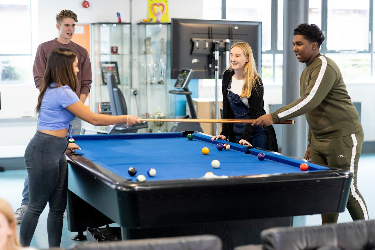 A group of young people are standing around a pool table. A young man and woman are hitting their pool sticks together. They are enjoying life being teetotal. This is a wide-angle image.