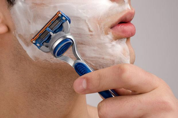 Man with shaving foam on his face beginning to shave with a razor