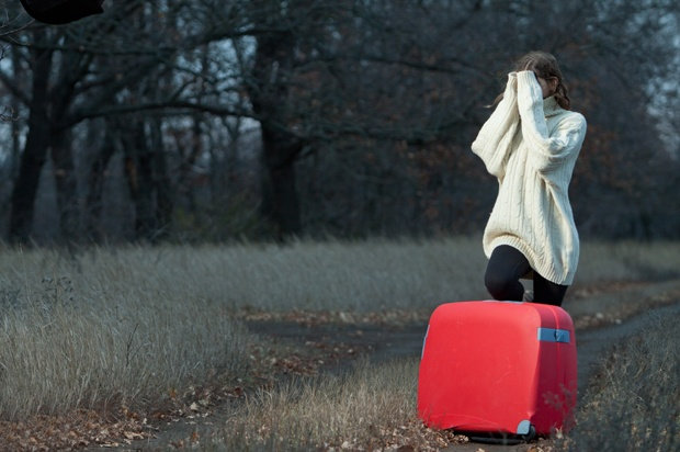 Girl with a big red suitcase in a field.