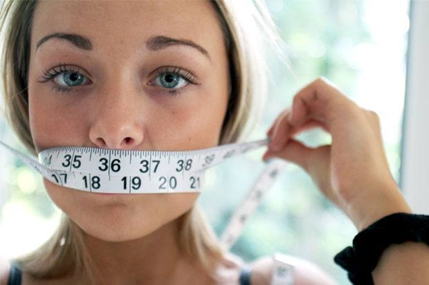 Girl with tape measure over her mouth