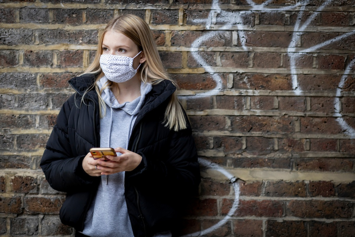 A young person is standing against a brick wall wearing a mask