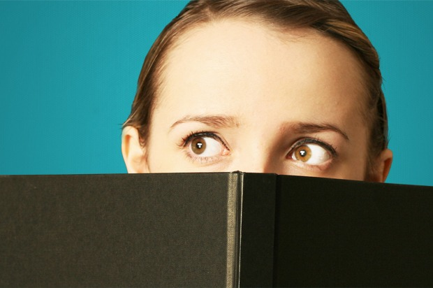 Girl peeping over a book