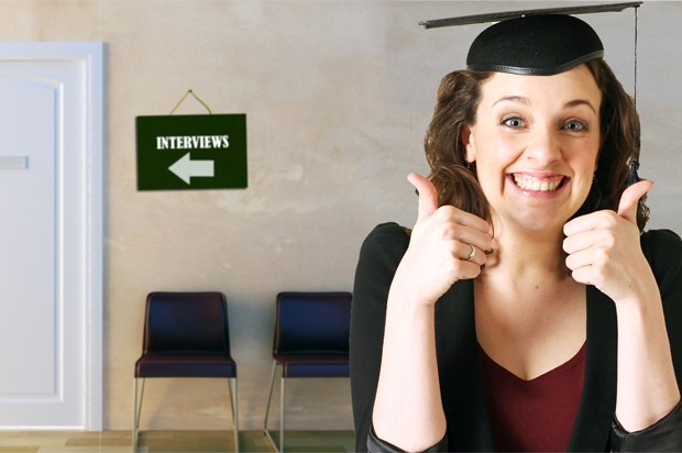 Girl outside of interview office wearing a mortarboard
