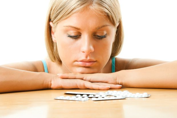 woman looking at packets of pills on a table.